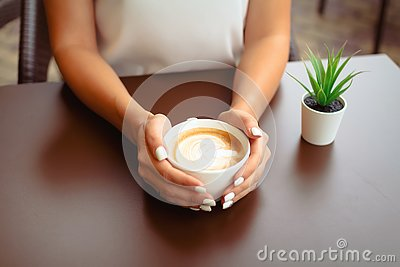 Woman hands holding cappucino or latte art.