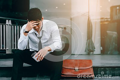 Asian young businessman stress sitting in front office with his