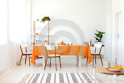 Long dining room table covered with orange tablecloth and comfortable white chairs