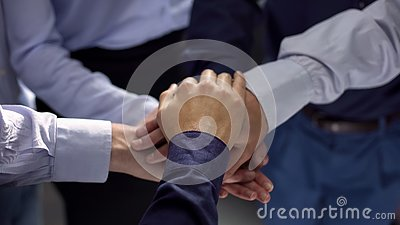 Group of business people stacking hands, team building training, cooperation
