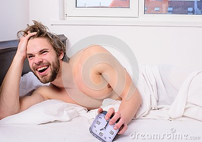 Enough sleep for him. Regulate your bodys clock. Man unshaven tousled hair wakeful face having rest. Good morning. Man
