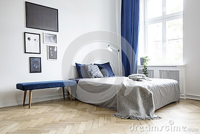 Natural light coming through a large window into a white and navy blue bedroom interior with cozy bed and wooden floor