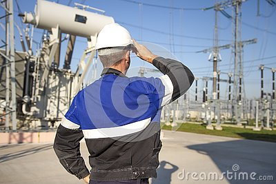 Electrician engineer on power electric station look at industrial equipment. Technician in helmet on electro substation