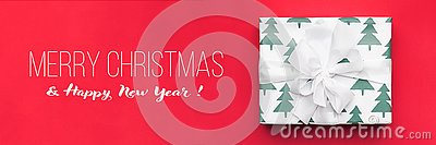 Christmas banner. Beautiful christmas gift isolated on red background. Wrapped xmas box. Gift wrapping.