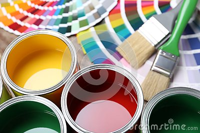 Paint cans, color palette samples and brushes on table