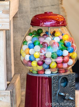 stock image of beautiful vintage candy vending machine, red, with old metal handle, full of colorful round candies