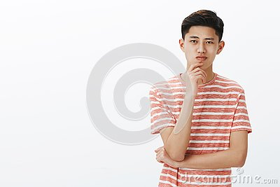 Smart and creative young asian guy thinking of new invention. Determined and ambitious attractive chinese male student