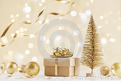 Christmas gift box against golden bokeh background. Holiday greeting card.