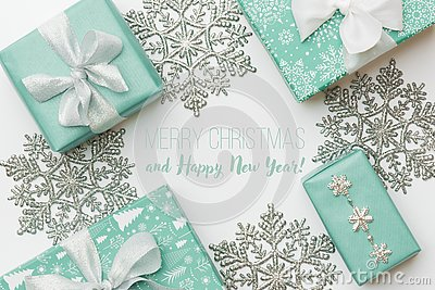 Beautiful christmas gifts and silver snowflakes isolated on white background. Turquoise colored wrapped xmas boxes.