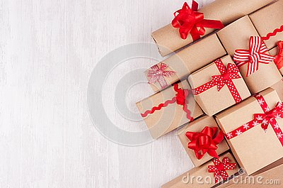 Festive craft paper gifts with red bows closeup on soft white wood board, top view, border.