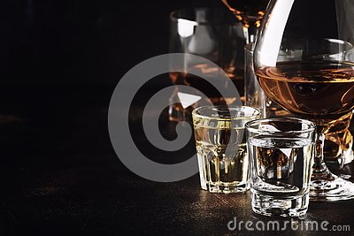 stock image of set of strong alcoholic drinks in glasses and shot glass in assortent: vodka, rum, cognac, tequila, brandy and whiskey. dark