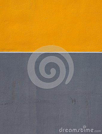 stock image of yellow and grey areas of paint on a rough textured concrete wall divided by a horizontal white stripe