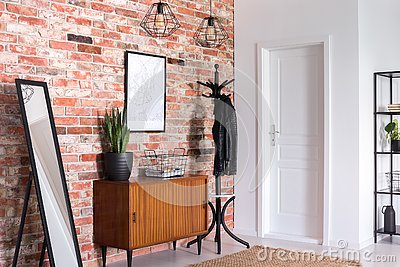 Mirror next to wooden cabinet in entrance hall interior with white door and poster on red brick wall