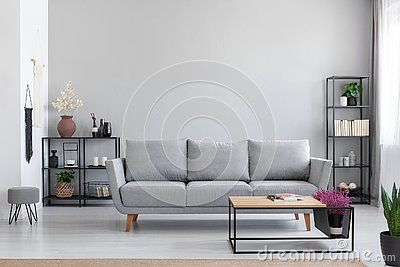 Flowers in wooden table in front of grey settee in modern simple apartment interior with stool