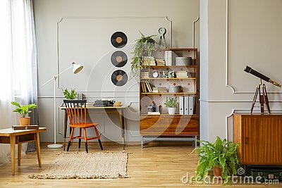 Vinyl records decorations on a gray wall with molding and wooden furniture in a retro home office interior for a writer. Real phot