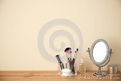 Makeup cosmetic products and tools in organizer on dressing table near color wall