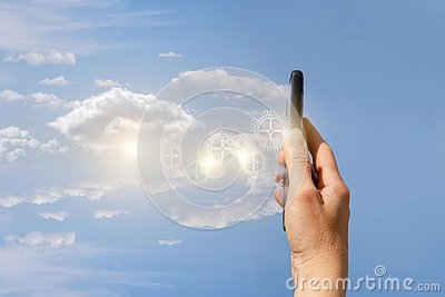 A hand holding a mobile phone emitting the mechanical details at the cloudy shiny background.