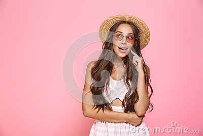Photo of stylish woman 20s wearing sunglasses and straw hat smiling at camera, isolated over pink background