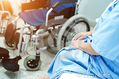 Asian senior or elderly old lady woman patient sitting on bed with wheelchair in nursing hospital ward : healthy strong medical co