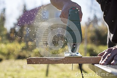 Man cuts wood product using an electric jigsaw joinery in the sun on a warm summer day.