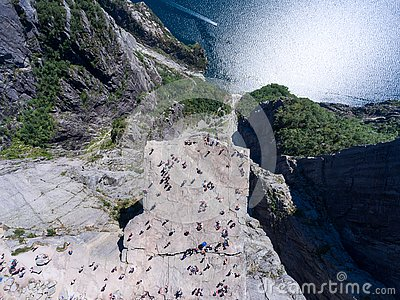 Flat rock Preikestolen over fjord Lysefjorden is natural attraction. Top view and flight up above cliff. Preacher`s Pulpit or Pre