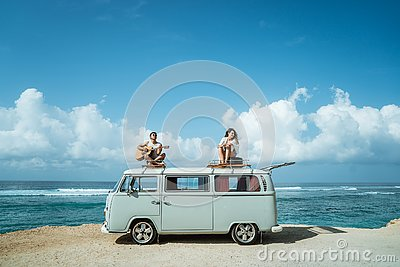 Hipster boy playing guitar with girlfriend on top of retro style