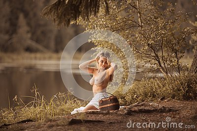 Attractive young woman with beautiful long blond hair sitting topless
