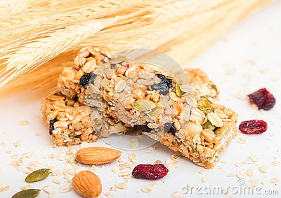 Homemade organic granola cereal bar with nuts and dried fruit on white background with oats and raw wheat.