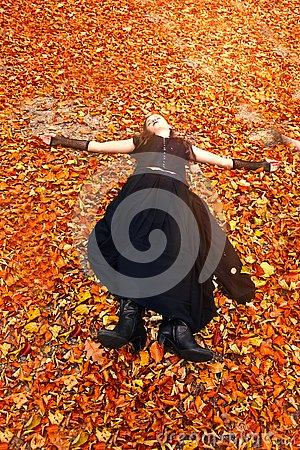 Girl enjoys the last sunbeams in orange autumn