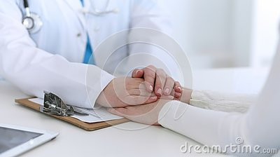 stock image of medicine doctor hand reassuring her female patient closeup. medicine, comforting and trusting concept in health care