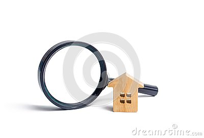 Wooden house and magnifying glass on a white background. Buying and selling real estate, building new buildings, offices and homes