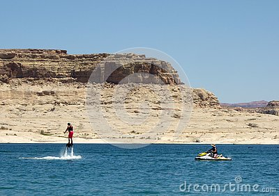 A man standing on jets of water at a reservoir in the desert