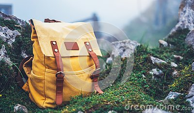 Hipster hiker tourist yellow backpack on background green grass nature in mountain, blurred panoramic landscape, traveler relax