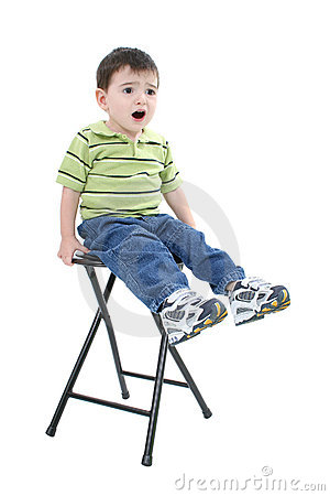 Adorable Boy Sitting On Stool With Upset Expression