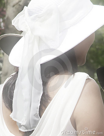 Back view of pretty woman wearing white hat