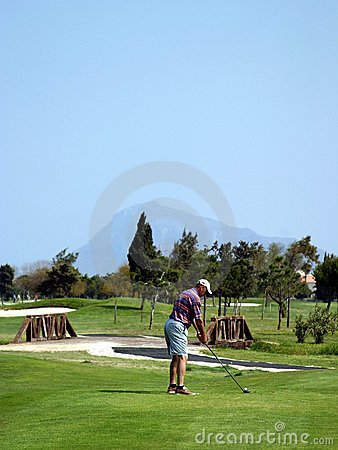 Man teeing off on golf course in sunny Spain