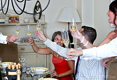 Smartly dressed people at a dinner party with Champagne