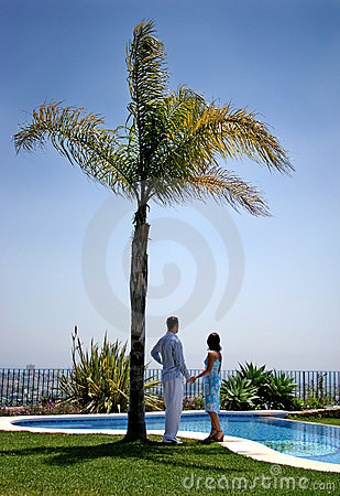 Young couple holding hands under a palm tree in the sun.