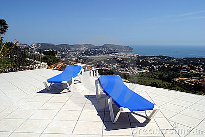 Two blue sunbeds on terrace in the sun with amazing views of the ocean