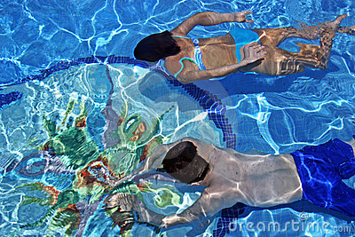 Couple swimming underwater in clear blue pool