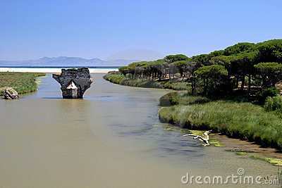 Old bridge on river leading to the sea in sunny Spain