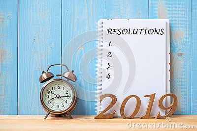 2019 Happy New years with Resolution text on notebook, retro alarm clock and wooden number on table and copy space