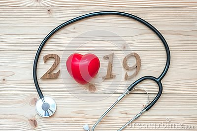 2019 Happy New Year for healthcare, Wellness and medical concept. Stethoscope with red heart and wooden number on table