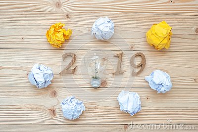2019 Happy New years with lightbulb with crumbled paper and wooden number on table. New Start, Idea, Creative, Innovation, Resolut