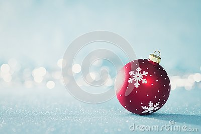 Bright Red Christmas Bauble in Winter Wonderland. Blue Christmas background with defocused christmas lights.
