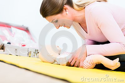 Woman in first aid course practicing revival of infant on baby d