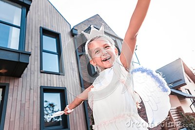 Cute beaming little girl feeling simply amazing while walking outside