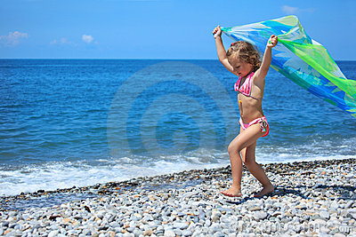 Little girl with fabric on stony seacoast