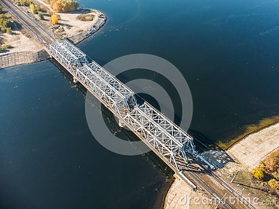 Aerial or top view of steel railroad bridge over river, train transportation concept