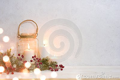 Christmas background, burning lantern candles decorated with frosted fir branches